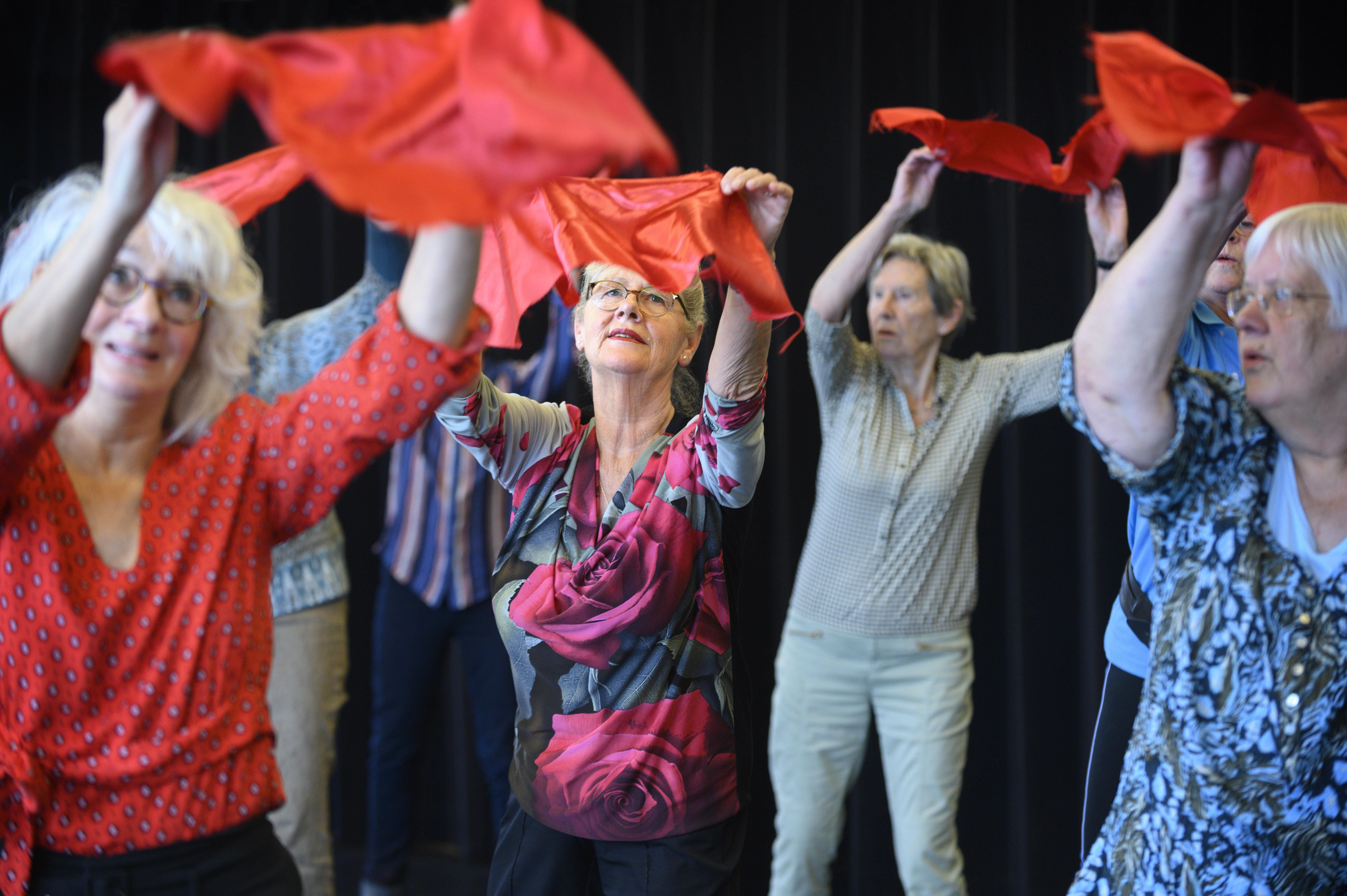 Senioren dansen met rode doeken boven het hoofd